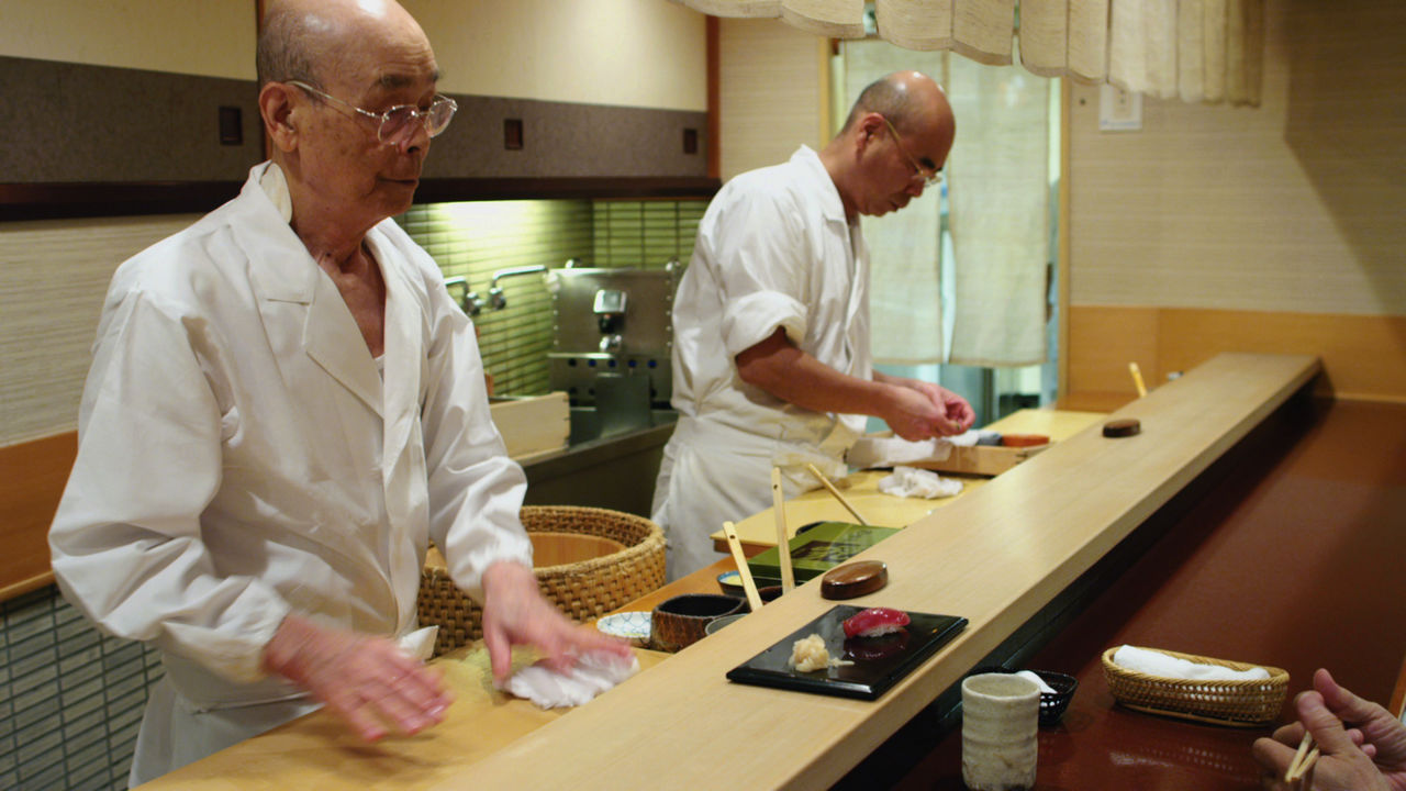 A group of people preparing food in a kitchen, with Jiro Dreams of Sushi